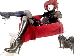 Crossdresser in boots, black corset, stockings and red dress